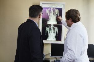 doctor-pointing-x-ray-result-beside-man-wearing-black-suit